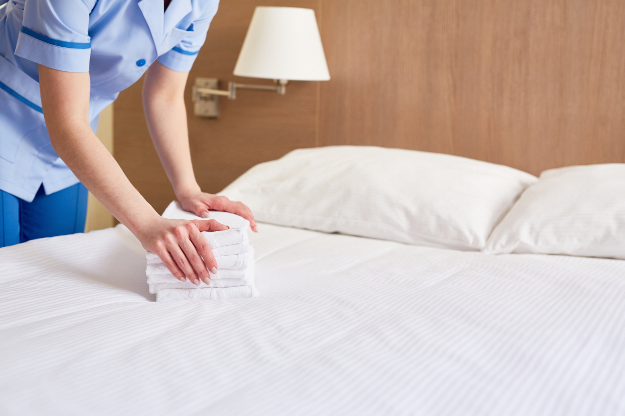 Hotel cleaner putting stack of white towels on bed